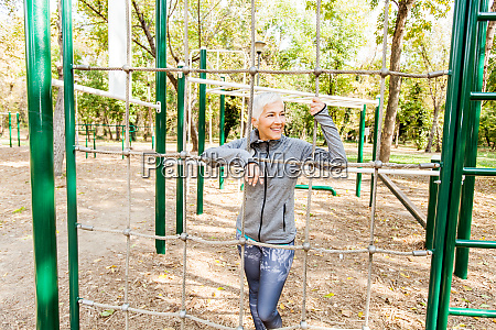 senior woman exercising at outdoor fitness