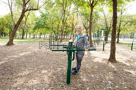 elderly woman exercising at public sports