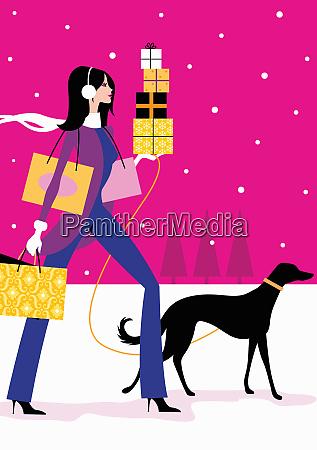 woman walking dog and carrying christmas