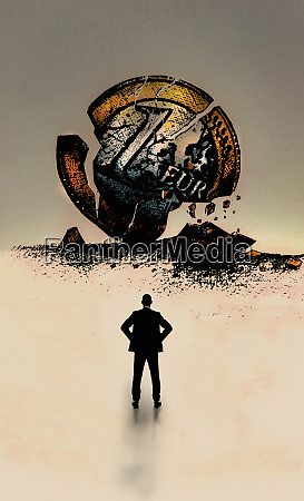 businessman looking at euro coin breaking