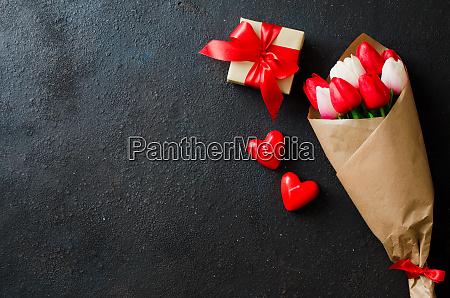bukiet tulipanow i pudelko na ciemnym