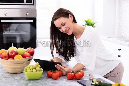 szczesliwa kobieta za pomoca cyfrowego tabletu