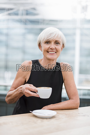 portrait of smiling senior woman drinking