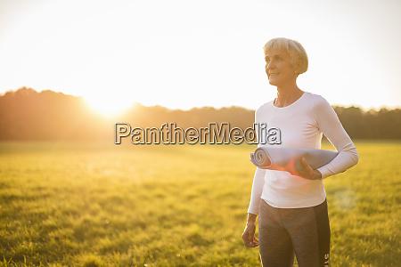 senior woman holding yoga mat on