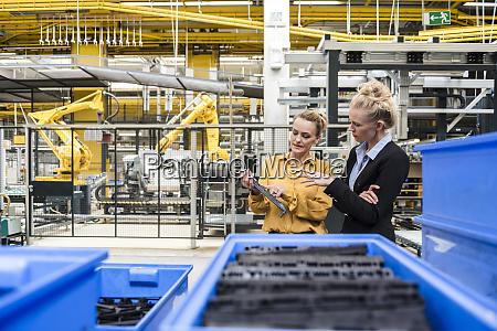 two women examining workpiece in factory
