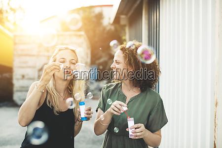 two happy women blowing soap bubbles