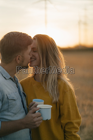 happy young couple holding mugs kissing