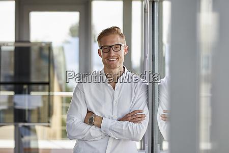 portret usmiechnietego biznesmena w biurze opierajacego