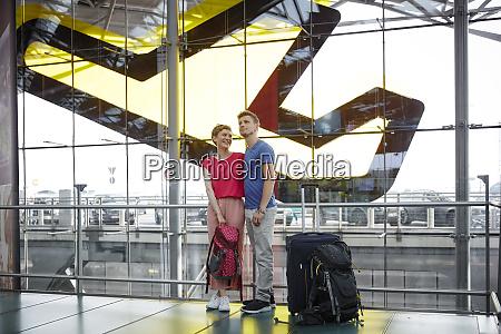 usmiechnieta para stojaca na lotnisku