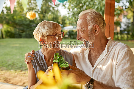 happy senior couple clinking beer bottles