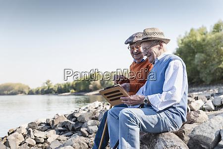 dwoch starych przyjaciol siedzi nad rzeka