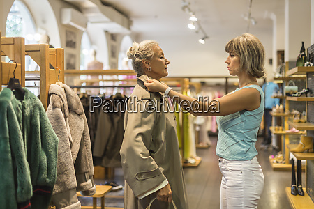 senior woman trying on coat in