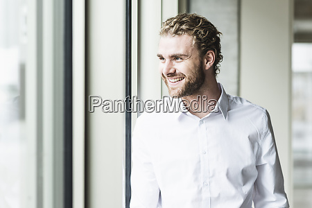 smiling young businessman looking out of