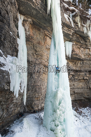 male ice climber ascending ice pinnacle