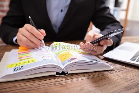 biznesmen holding cellphone pisanie harmonogramu w