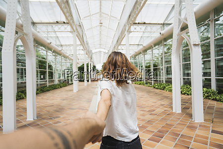 woman holding hand ofc man in