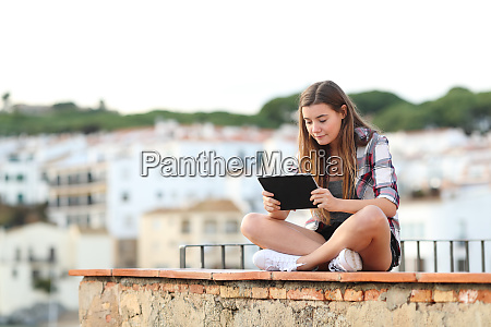 serious girl using a tablet sitting