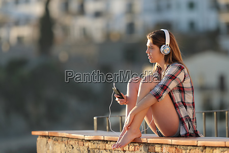 relaxed teen listening to music sitting