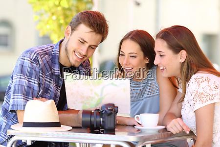 trzy turysci planowania podrozy w barze