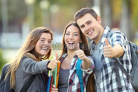 trzy szczesliwy studenci z kciuki w