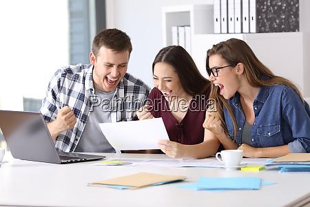 podekscytowani pracownicy czytajac dobry raport wynikow