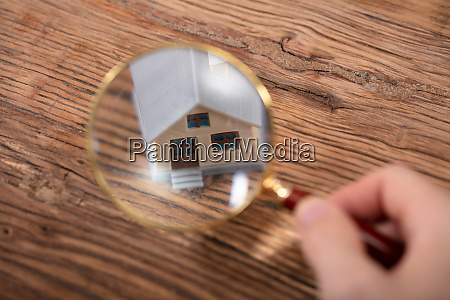person holding magnifying glass over house