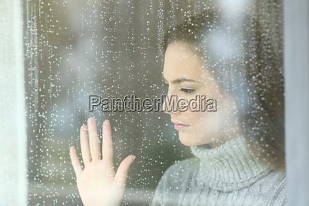 smutna dziewczyna patrzac przez okno w