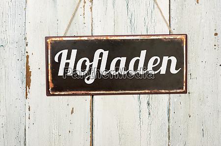 stary metalowy znak przed biala drewniana