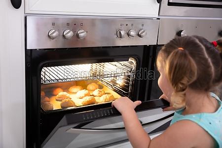 dziewczyna pieczenia ciasteczek w piekarniku