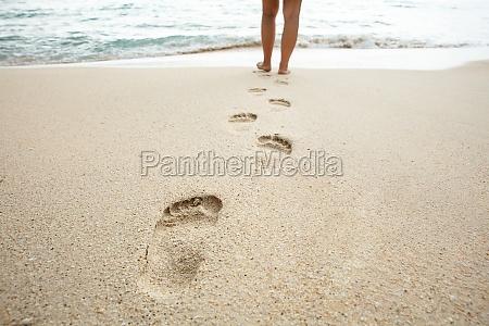 kobieta spaceru na plazy pozostawiajac slady