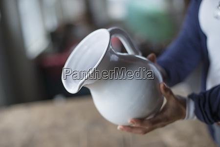 kobieta trzymajaca bialy dzbanek z ceramiki