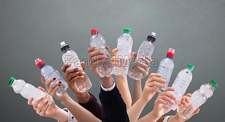 rozni ludzie trzymajacy butelki z woda