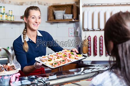 sprzedawca w sklepie miesnym oferuje jedzenie