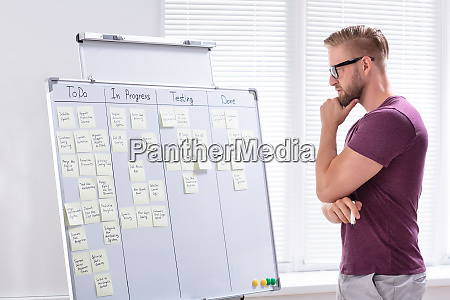 businessman looking at adhesive notes in