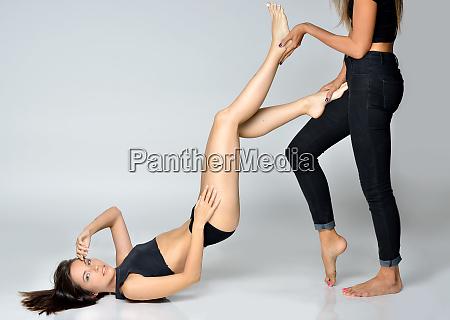 dwie piekne kobiety robia razem cwiczenia