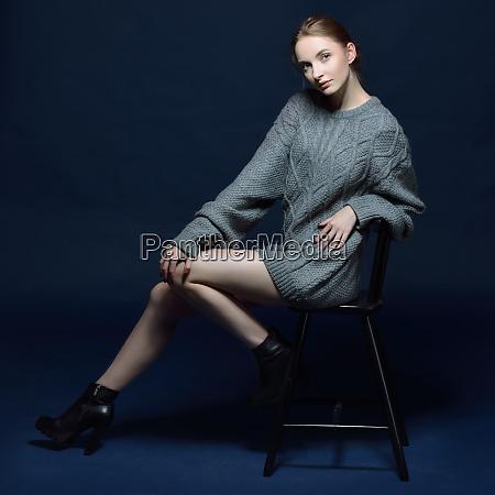 beautiful woman in sweater in studio