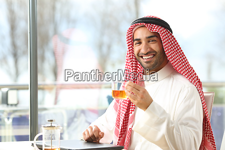szczesliwy arabski czlowiek trzymajacy filizanke herbaty