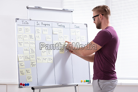 young businessman writing on sticky notes