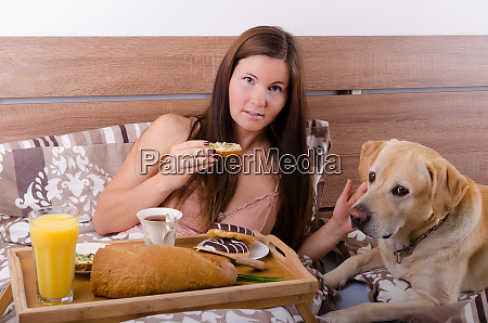 beautiful young woman eating breakfast in