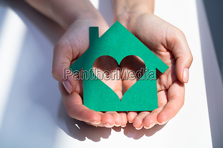 womans hand holding green paper house