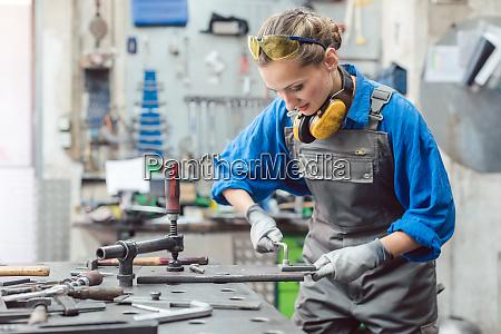 kobieta mechanik pracuje w warsztacie metalowym