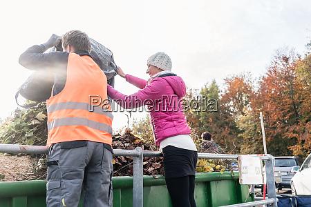 kobieta i mezczyzna dajacy odpady zielone