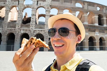 man eating italian pizza near colosseum