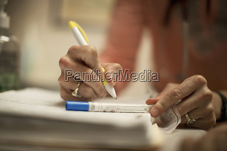hands of a female doctor writing
