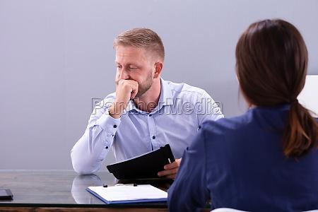rozczarowany mlody czlowiek siedzi na rozmowie