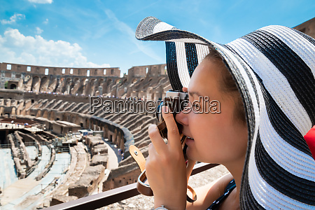 woman taking photo of colosseum