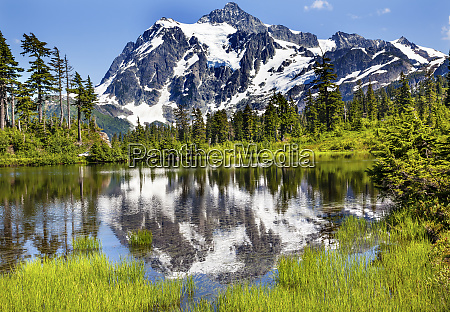 mount shuksan reflects into picture lake