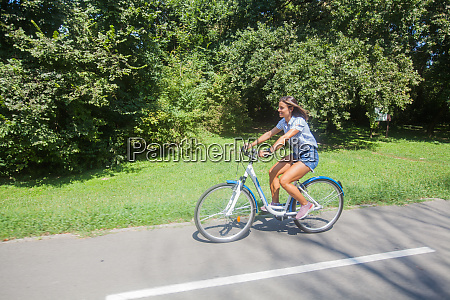 young woman riding bicycle in