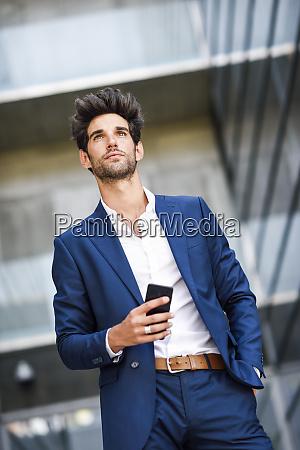 biznesmen z telefonem komorkowym poza budynkiem