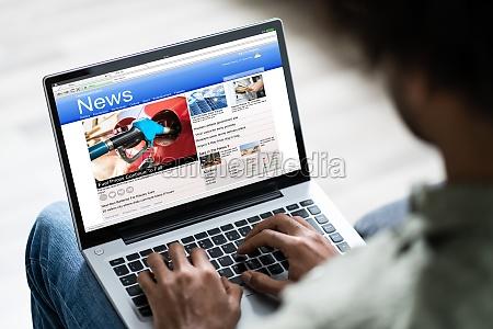 czlowiek ogladanie online aktualnosci na laptopie